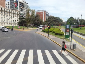 Garota atravessando uma faixa de pedestres. Vê-se uma calçada com faixa de passeio e serviço.